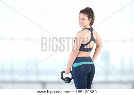 Fit woman working out with a kettlebel and similingl in a gym