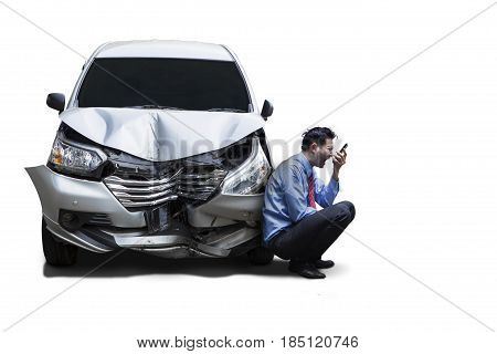 Picture of angry businessman sitting next to a damaged car while talking on his cellphone isolated on white background