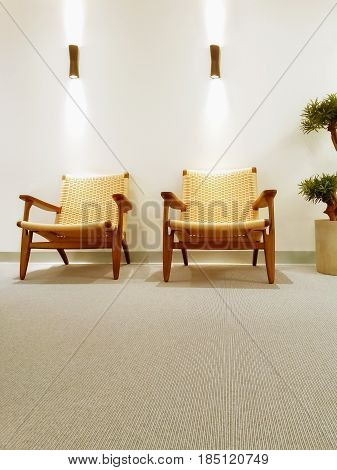 Interior with classic rattan chairs and carpet floor.