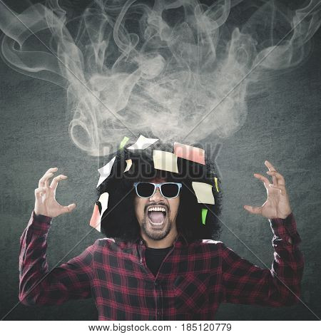 Photo of anxious Afro wearing sun glasses while screaming at the camera with smoke and empty post it on his curly hair