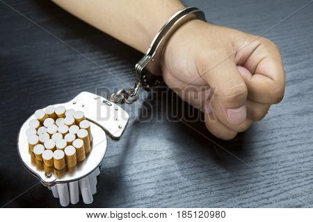 Arm of man and cigarettes is bonding with a handcuffs on the wooden table