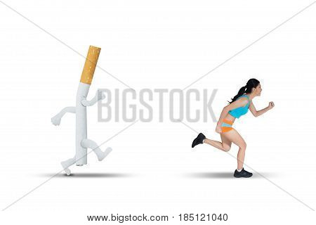 Image of Asian woman wearing sportswear while running away from a cigarette in the studio