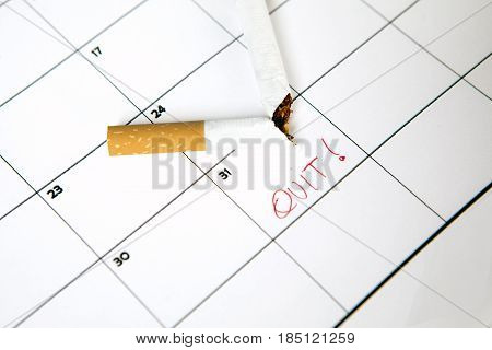 Broken cigarette on calendar with quit word concept of quit smoking