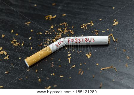Picture of a broken cigarette with a word of impossible changed possible on the wooden table