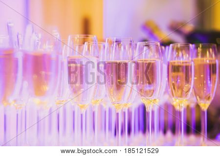 Beautiful row line of different colored alcohol cocktails on a party, martini, vodka,and others on decorated catering bouquet table on open air event, picture with beautiful bokeh