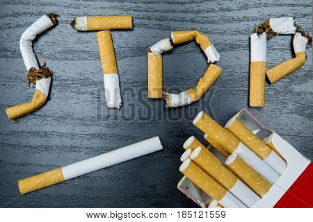 Concept for quitting smoking. Cigarette butts shaped a Stop smoking word on the wooden table
