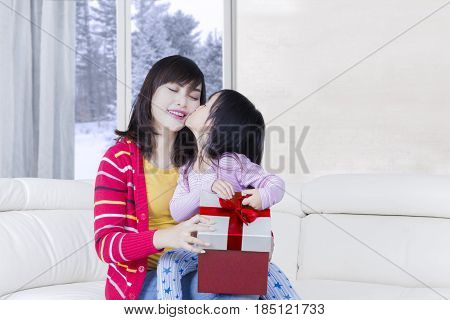 Little daughter holding a gift box while kissing her mother cheek with winter background on the window
