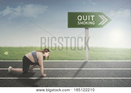 Image of fat woman in ready position for running with text of quit smoking on the signpost