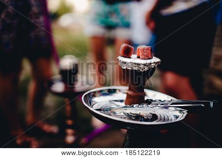 Red-hot coals for hookah against the background of group of friends. Conception is recreation on the landscape, campaign, camping, holidays