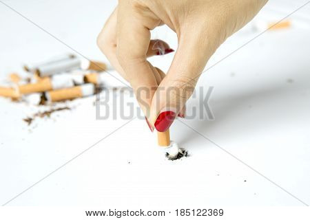 Female hand breaking a cigarette concept of quit smoking isolated on white background