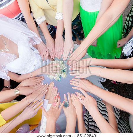 wedding. The girlfriends of the bridesmaid sent their hands in a circle. Bridal bouquet. Friends
