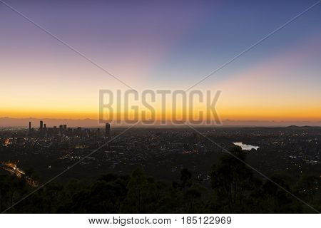 First light beaming colourful rays over Brisbane cityscape, viewed from Mt Coot-tha lookout