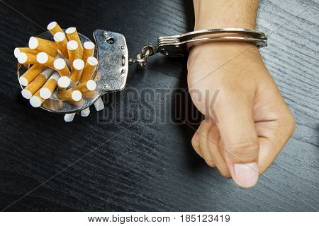 High angle view of man's arm bonding cigarettes with a handcuffs on the wooden table