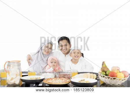 Muslim family having meal at dining table while smiling at the camera isolated on white background