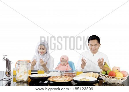 Muslim family praying before having meal while sitting in front of dining table isolated on white background