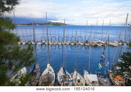 Two lines of yachts at peer of the coastline facing mountains