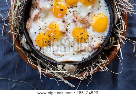 Fried eggs on a cast-iron frying pan. Scrambled eggs from quail eggs on a serving table. Close-up.