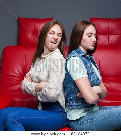 Two quarreling girls sits on red leather couch