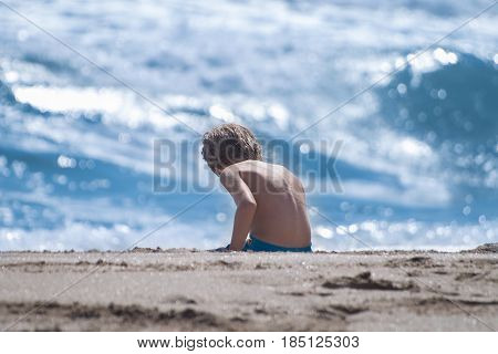 Boy sitting on sand at beach on sunny day