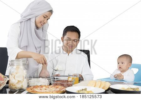 Beautiful wife wearing muslim clothes preparing food for her family at dining table isolated on white background