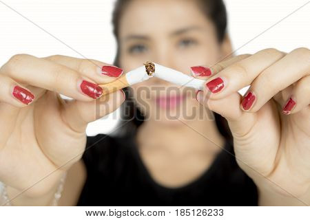 Woman hand breaking a cigarette concept of quit smoking isolated on white background