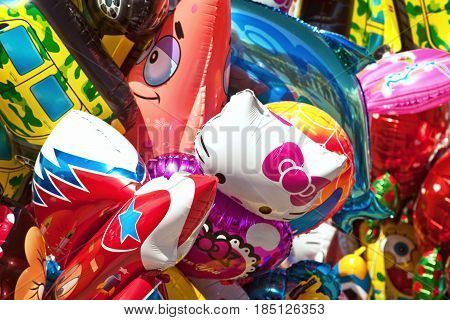 Khabarovsk Russia - May 1 2017: Bunch of various cartoon characters balloons at fair. Hello Kitty Patrick Star and other colorful fun balloons background