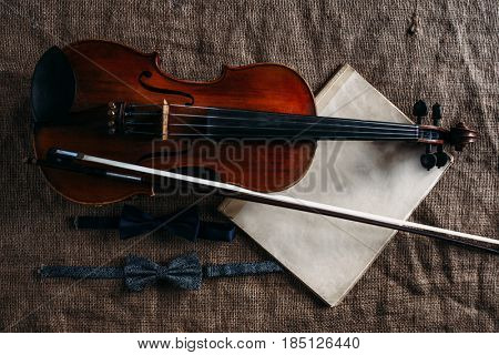 Violin, fiddlestick, notes and bowties closeup