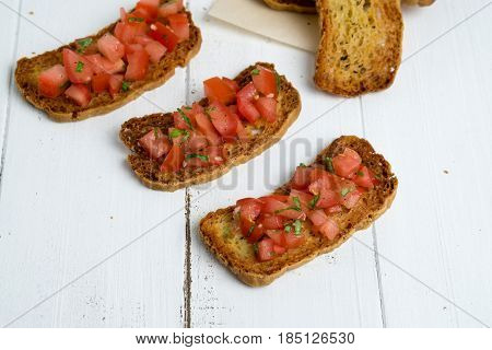 Bruschetta on white background. Bruschetta is a popular Italian appetizer (antipasto) made of a crostini (grilled bread) with a topping made of diced tomatoes olive oil herbs (basil) and garlic. A simple and delicious snack!