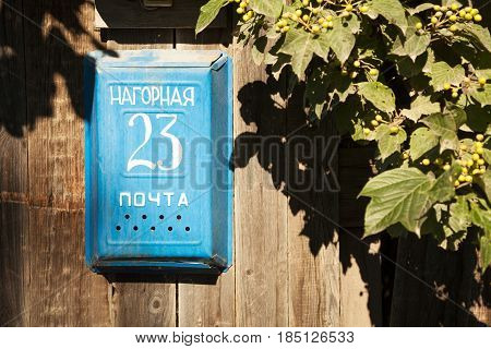 Old blue mailbox on a wooden fence next to green foliage at Russian countryside. 23 numbers and address on a metal mail box with text: 23 Narognaya street / mail