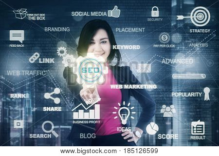 Picture of a young female entrepreneur pressing a SEO icon on the virtual screen. Concept of Search Engine Optimization