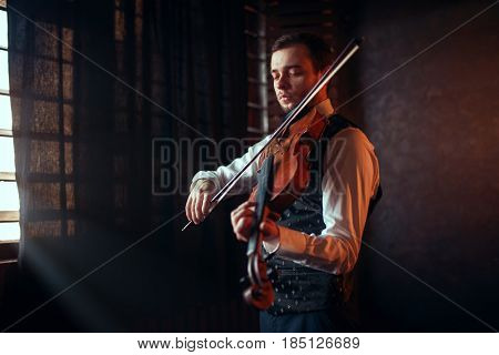 Male fiddler playing classical music on violin