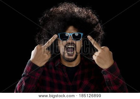 Young man showing middle finger as his angry expression while wearing sun glasses with dark background