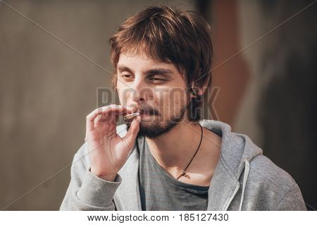 Closeup Of Young Man Smoke Marihuana Grass Or Hashish Joint