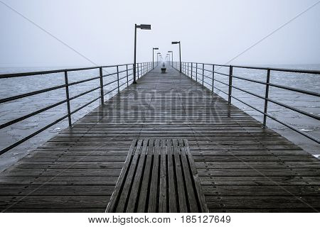 Long Foggy Pier. Pier on the Great Lakes shore disappears into a dense fog on the coast of Lake Huron in Harbor Beach, Michigan.