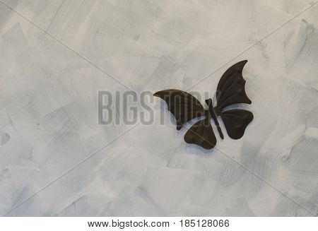 Iron butterfly on cement background, metal background