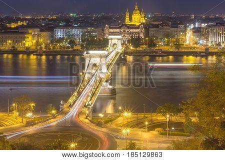 View of Chain Bridge and St. Stephen's Basilica at night Budapest Hungary