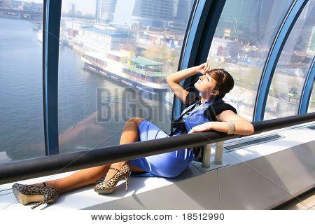 Smiling girl incumbent indoor blue glass corridor