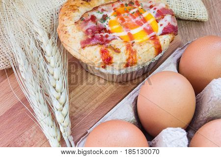Baked sandwich with egg cheese and ham. Hot breakfast. Bun with liquid egg ham and melted cheese on natural wooden background.
