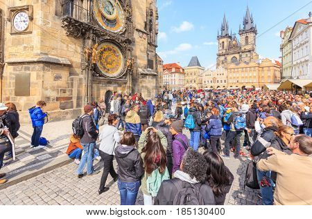 PRAGUE CZECH REPUBLIC - APRIL 15, 2016: Group of people in the Old Town Square in front of Tyn Church and famous Astronomical Clock.