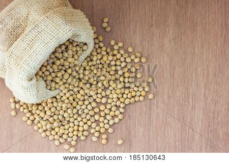 Soybean in hemp sack bag on a wooden background.