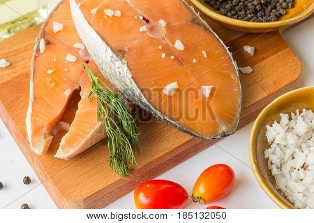 fresh fish salmon raw salmon steak with sea salt pepper and Dill Weed isolated on a white background