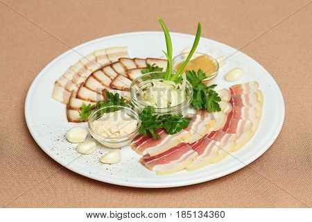 Plate with meat cutting strips of bacon and sliced lard sauce greens
