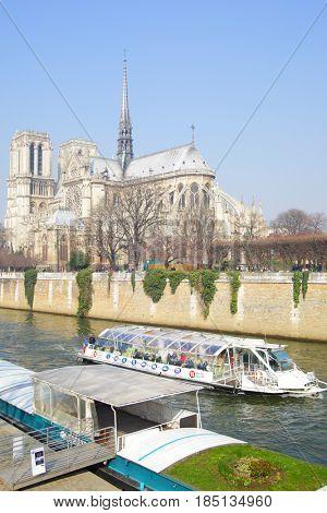 Paris, France - March 05, 2011: Tourist hop on hop off boat near Notre Dame de Paris