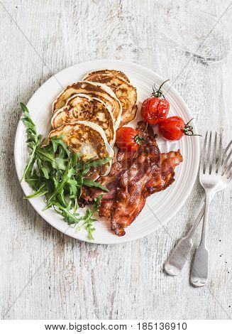 Traditional american breakfast - crispy bacon pancakes with maple syrup roasted tomatoes arugula. On a light background top view