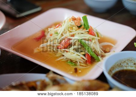 Famous Thai food papaya salad or SOM TAM on wood table