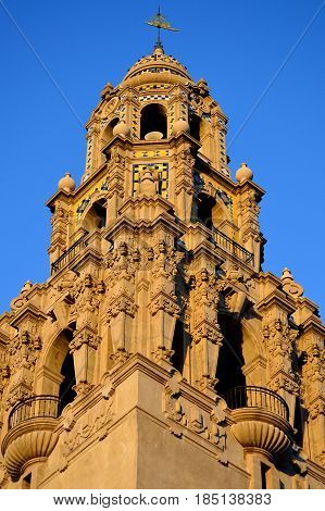 A well lit and ornate cathedral tower stands against a briliant blue sky. Balboa Park