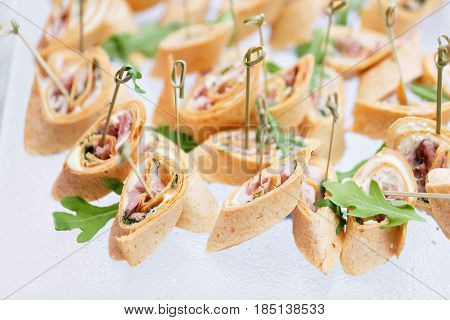Assorted canape with cheese, meat, rolls and fruit salad. Food to accompany the drinks. the buffet at the Banquet. A reason to celebrate the event. Wedding or anniversary.