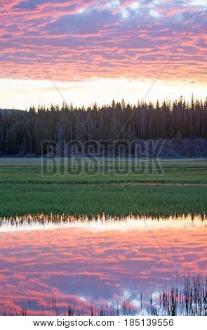 Sunrise cloudscape reflections over Pelican Creek in Yellowstone National Park in Wyoming USA