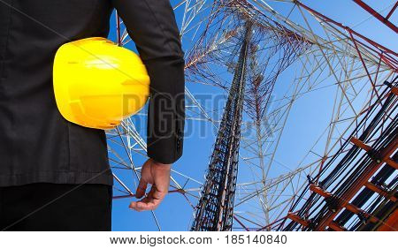 businessman in suite with yellow safety helmet with telecommunication tower with blue sky background business technology industrial concept.