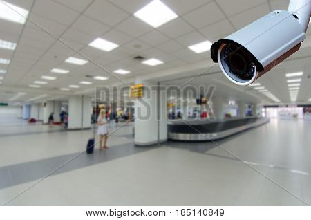 security CCTV camera with abstract blurred people waiting for luggage or bag in airport business or tourism travelling and security technology concept.